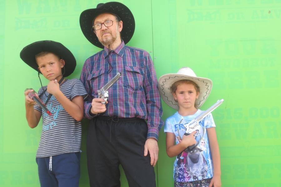 Виктор Барабанов, его внук Кирилл и внучка Полина играют в ковбоев.